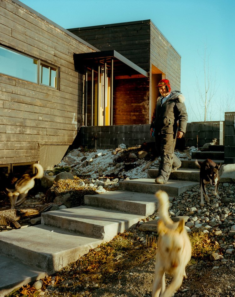 Perched on top of a hill, the house is accessed by a long staircase that runs up to the exterior courtyard. The dogs, naturally, take their own route. Tagged: Outdoor and Walkways.  Photo 25 of 25 in 25 Dogs Living in the Modern World from This Modern Cabin Is the Ideal HQ For a Family in Alaska