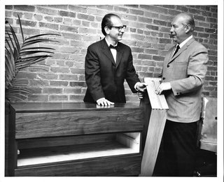 Mel Smilow, left, and Morton Thielle demonstrate the solid wood slide and groove construction of a drawer inside one of their creations (cheaper furniture uses metal slides). Photo courtesy of the Smilow Family.