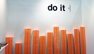 Do It: The Compendium by Hans Ulrich Obrist - Photo 7 of 11 - Making a splashy entrance at this year's NADA Art Fair, do it's booth created a wall-to-wall forest of orange tomes and installations for visitors to peak at.