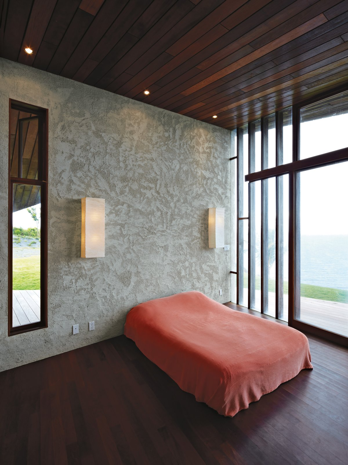 In the master bedroom, a basic platform bed and Ikea wall lights keep the attention on the ocean views afforded by the floor-to-ceiling windows. Tagged: Bedroom, Bed, Dark Hardwood Floor, and Wall Lighting.  Photo 9 of 10 in Clifftop House with Angled Roof in Maui