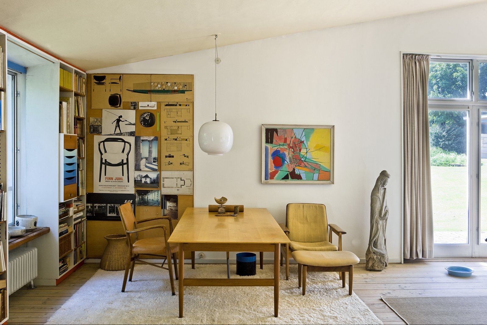 Architectural ispiration and exhibition posters fill the walls of Juhl's home office. Two chairs of Juhl's design are placed on the side of his desk, designed in 1945.  Midcentury Homes by Dwell from The Highly Personal House of Danish Design Great Finn Juhl