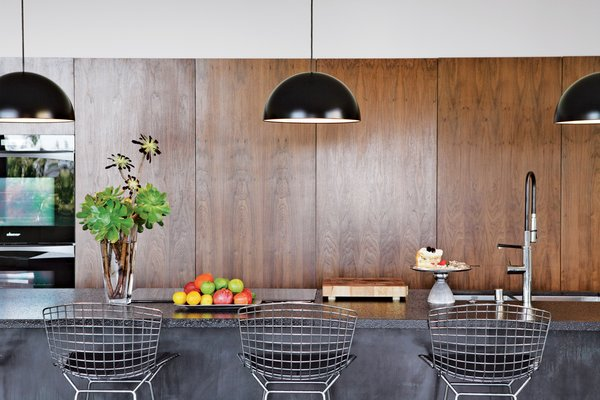 In the kitchen, custom walnut cabinetry and Caesarstone counters are paired with Bertoia stools and Ikea pendant lamps.