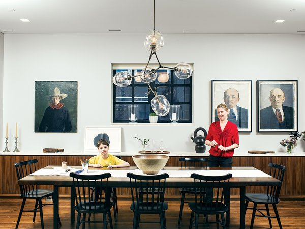In the dining area of the kitchen, Design Within Reach's Salt chairs surround a vintage Milo Baughman table. The Lenin portraits on the wall behind Jen and Jonas were purchased from Steven Sclaroff and form an ironic counterpoint to the family's assembled Americana.