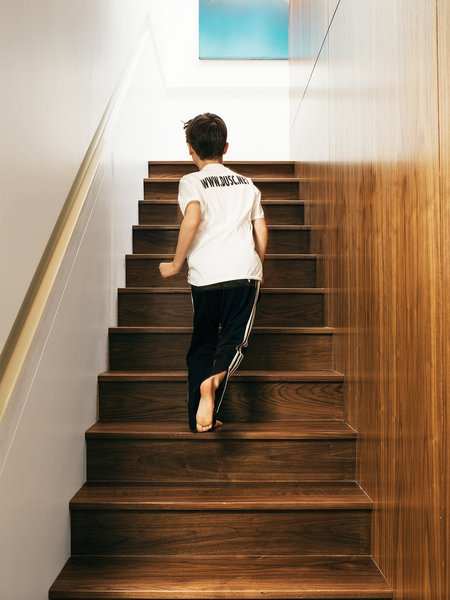 Jonas runs up the custom walnut stairwell, with inset Corian handrail, that leads up to the second-floor master suite.