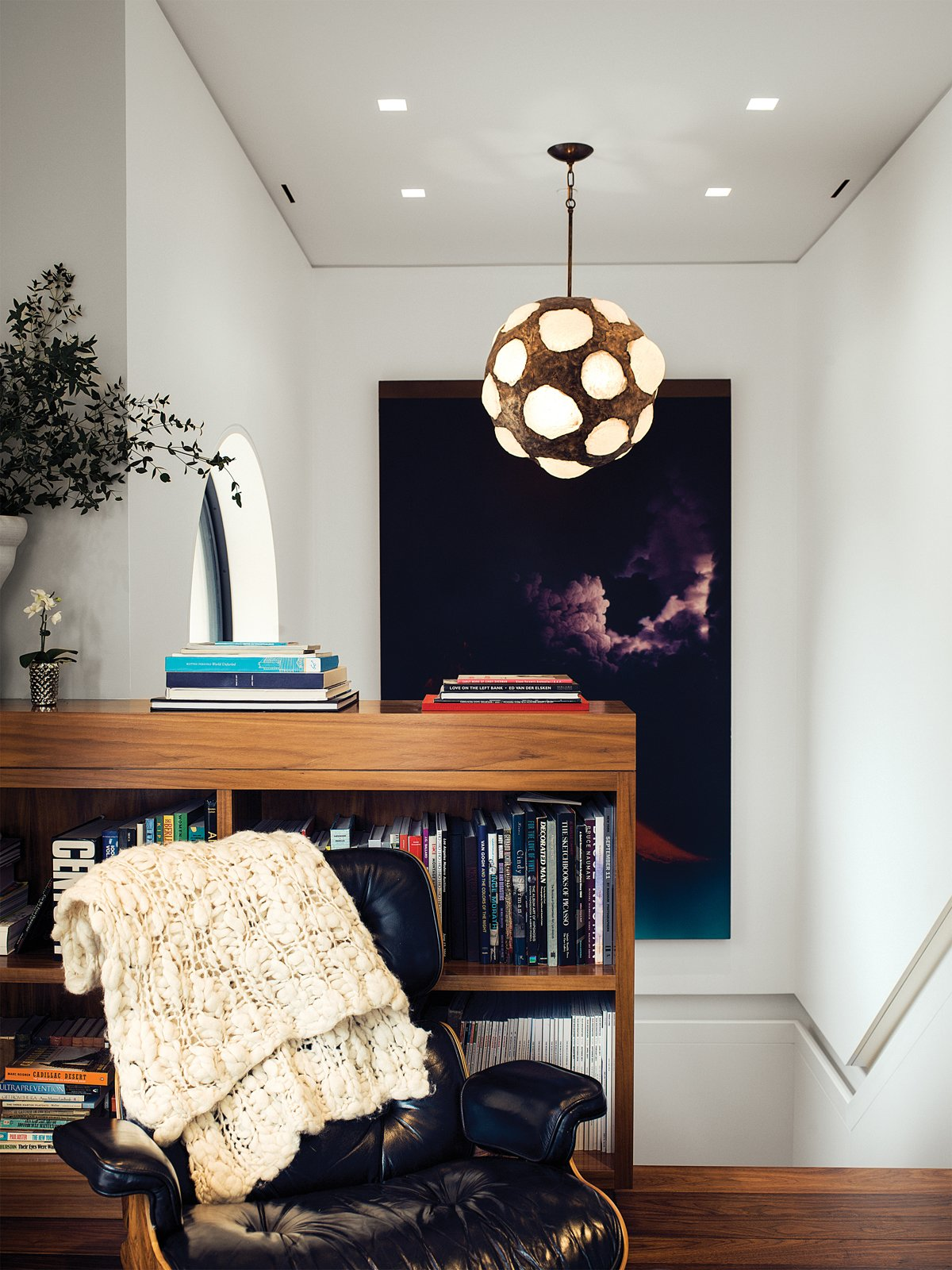 At the top of the stairwell, a sitting area is outfitted with a vintage Eames lounge, a large Jack Goldstein painting, and a 1970s light fixture found by Marcovitz in Paris.