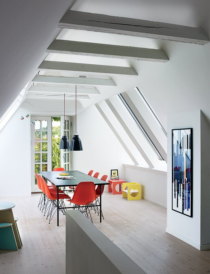 Charrier transformed a cramped attic into a sunny dining room with Vitral windows and white-tinted pine floors by Dinesen. The Sara table is by Hay, the Shell chairs are by Charles and Ray Eames, and the artwork is a hand-printed textile she had framed. Tagged: Dining Room, Pendant Lighting, Ceiling Lighting, Table, Chair, and Lamps.  Modern Danish Homes We Love by Aileen Kwun from A Cramped Attic Became a Sunny Dining Room in this Renovation of a Copenhagen Tudor