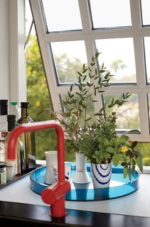 A red Vola faucet adds color, while the muntin bars on the windows recall the originals.