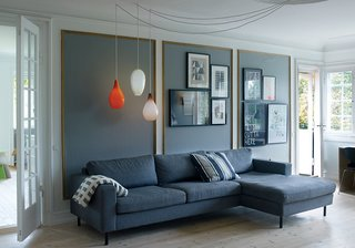 The living room features a roomy Scandinavia sofa from Bolia and vintage glass pendants from Holmegaard. The original gold stucco wall frames are accented with Farrow & Ball paint in Mole's Breath.