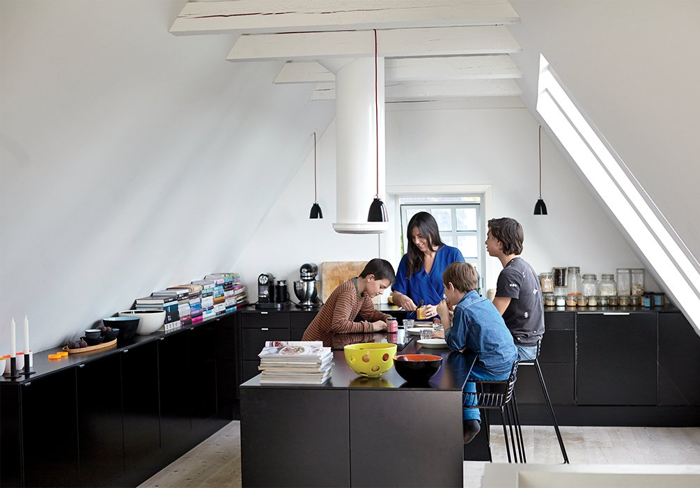 With three sons in the family, the kitchen gets a lot of use. Hee barstools by Hee Welling for Hay slide up to a multi-functioning island where the family gathers to eat, study and play. Tagged: Kitchen, Pendant Lighting, and Ceiling Lighting.  Photo 9 of 12 in A Cramped Attic Became a Sunny Dining Room in this Renovation of a Copenhagen Tudor