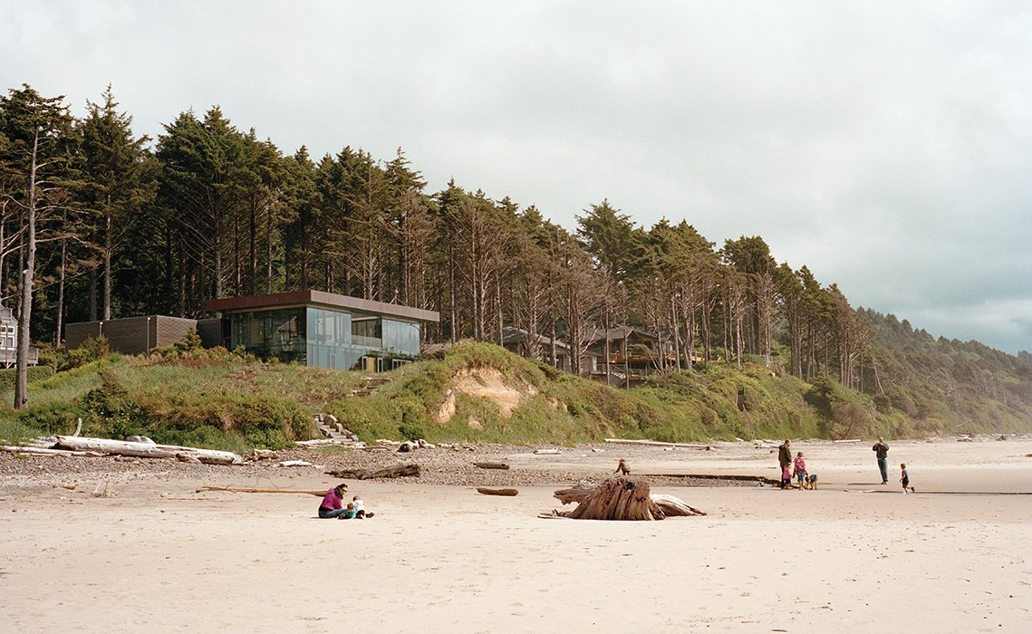 Boora Architects designed a house for Ryan and Mary Finley near Cannon Beach, Oregon, that resembles a glass prism and rises above a shallow cliff overlooking the Pacific Ocean. The 3,330-square-foot structure is topped with a green roof. Tagged: Exterior, Glass Siding Material, House, and Flat RoofLine.  Photo 1 of 9 in Glass House with Stunning Pacific Ocean Views