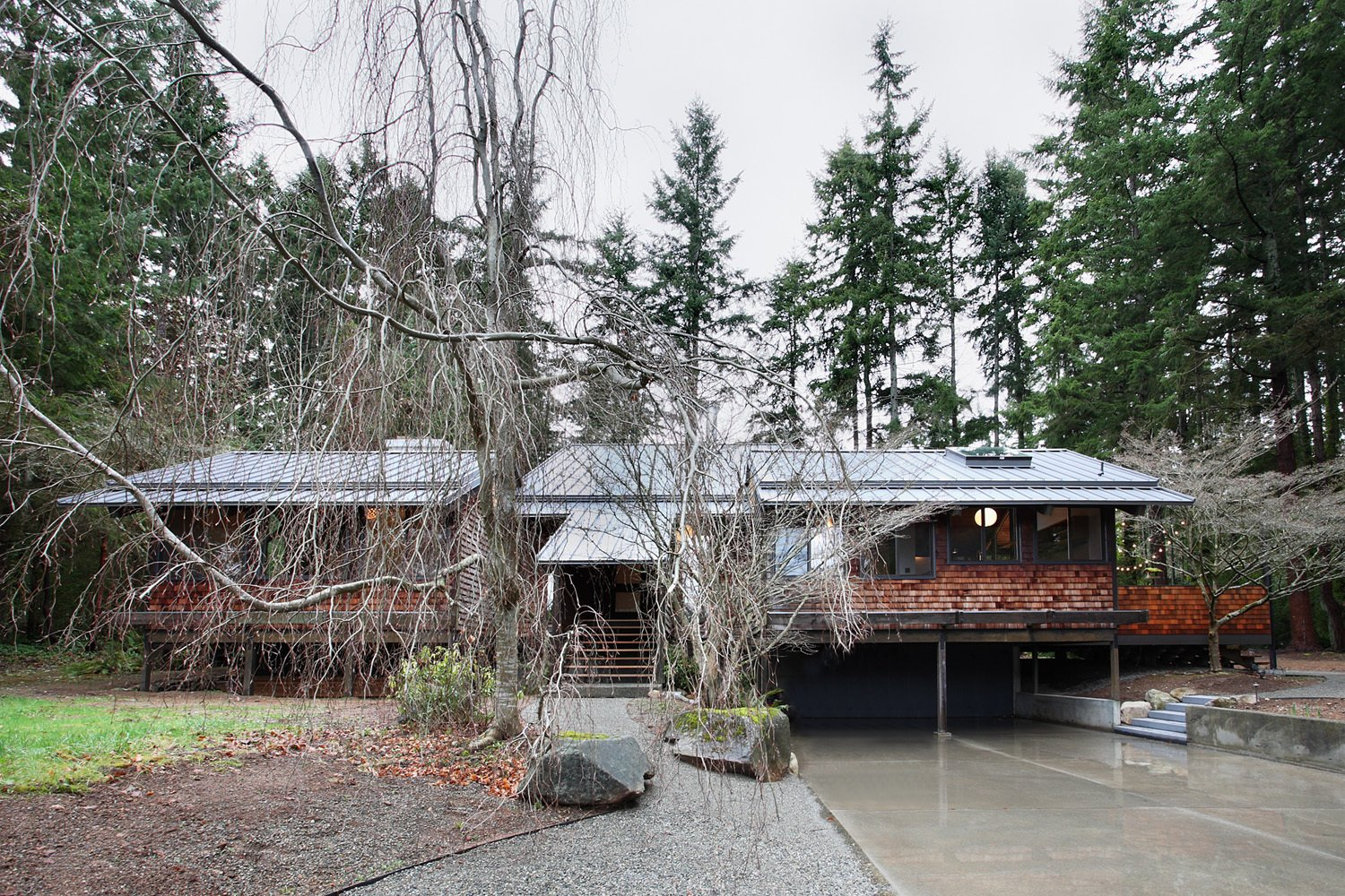 Nestled in a grove of Douglas fir trees, the house stands on series of wooden pylons in a Japanese-inspired fashion. Residents ascend the stairs, center, to reach its single floor. The exterior wooden shingles were intact and are original to the design.