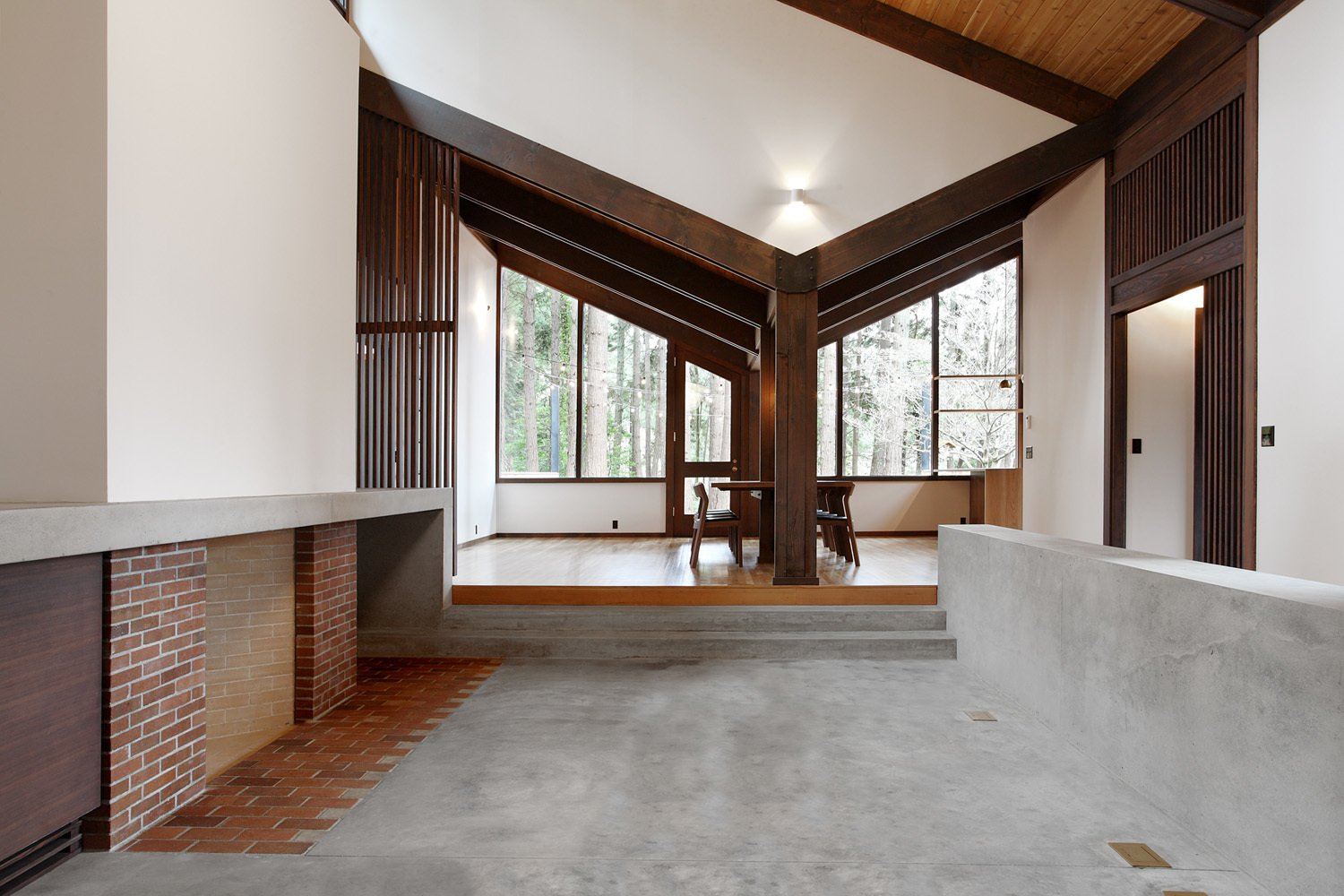 The dining room opens up to the new concrete hearth. Old plans indicate this area was originally intended to be an open courtyard, however, the original clients enclosed it with a leaky glass canopy. The architects installed a new sloped roof that quickly channels away rainfall. The fireplace is composed of brick salvaged from the original floor and the new concrete floor features increased insulation.  Midcentury Homes by Dwell from Zema Redux