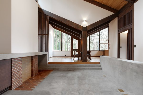 The dining room opens up to the new concrete hearth. Old plans indicate this area was originally intended to be an open courtyard, however, the original clients enclosed it with a leaky glass canopy. The architects installed a new sloped roof that quickly channels away rainfall. The fireplace is composed of brick salvaged from the original floor and the new concrete floor features increased insulation. Photo 6 of Zema Redux modern home
