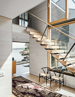 8 Bright and Airy Wood-Paneled Spaces - Photo 8 of 8 - To create continuity between inside and out without overpowering guests and residents, the interiors of this home in Connecticut are clad in bleached white cedar boards, while the exterior is sheathed in more traditionally unfinished cedar boards that can age over time. The lighter finish on the interior feels beachy and relaxed, and acts as a neutral foil for traditional and modern furnishings.
