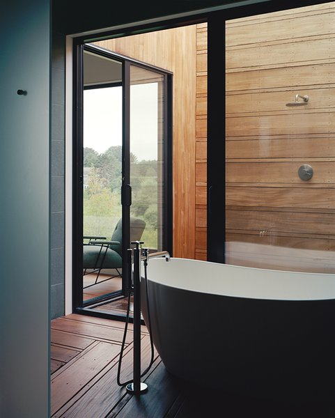 The master suite's bathroom unfolds from a glass-walled bathing room, outfitted with a Signature Hardware tub and Lefroy Brooks fixtures, to an open-air shower.