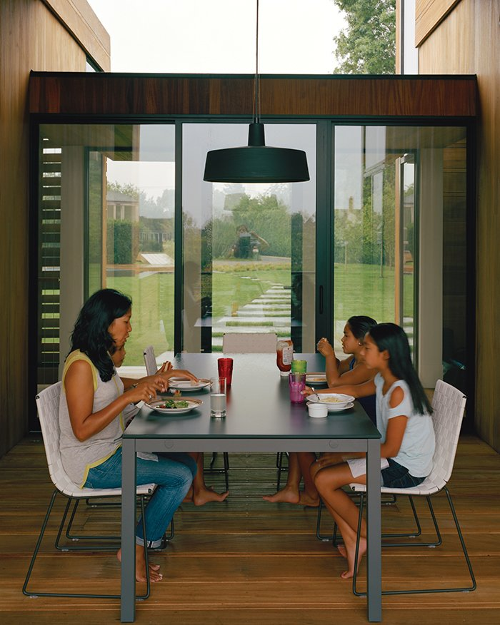 For the outdoor dining room, interior designer Damon Liss selected a Soho pendant lamp by Joan Gaspar, Trennza chairs from Janus et Cie, and the Portica outdoor table from Room & Board. The sliding glass doors are by Arcadia. Tagged: Dining Room, Pendant Lighting, Table, and Chair.  Photo 6 of 9 in Modern Wood-Lined Family Home in the Hamptons