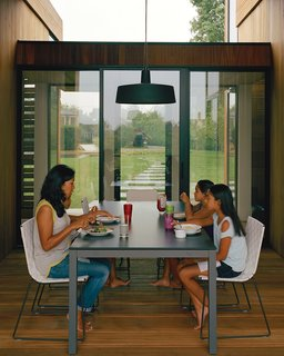 Modern Wood-Lined Family Home in the Hamptons - Photo 6 of 9 - For the outdoor dining room, interior designer Damon Liss selected a Soho pendant lamp by Joan Gaspar, Trennza chairs from Janus et Cie, and the Portica outdoor table from Room & Board. The sliding glass doors are by Arcadia.