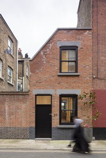 A Spotlight on 10 Traditional Homes with Modern Interiors - Photo 9 of 20 - Set in a conservation area, the home's façade was designed to blend into the street's terrace style. To that end, it is clad in red bricks from Traditional Brick & Stone and punctuated with sash windows. The concrete toned lintels hint subtly at the modernity that lies within.