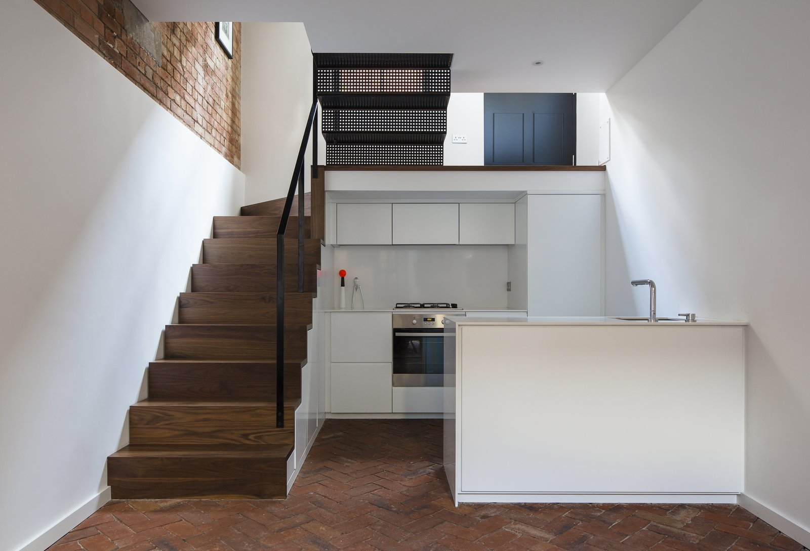 The kitchen is situated in a sunken basement, underneath the staircase's walnuts steps. The same joiner who built the house's timber elements built the white cabinetry which are finished in a 40% gloss lacquer. Silestone countertops and integrated appliances maintain the space's simple lines. Additional storage is fitted under the staircase. Tagged: Staircase, Metal Tread, and Wood Tread.  Cleverly Stacked Floors Form a Roomy House On a Tight Lot by David Rudin
