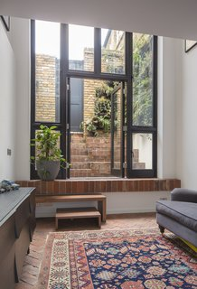 10 Indoor-Outdoor Homes in London - Photo 4 of 10 - The home's living room is located on the lower level, opposite the kitchen. The herringbone-patterned brick floor is partially covered by a carpet purchased in Istanbul. A sofa and Muuto sideboard anchor opposite sides of the space.