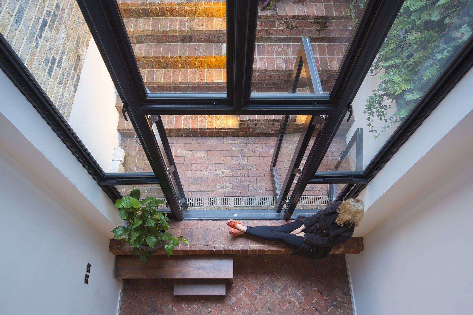 Viewed from above, the lower level's brick floors establish a sense of continuity between the living spaces and the outer courtyard. Two-stories of glazing ensure that the lower levels never feel gloomy.  Brick Houses from Around the World  by Matthew Keeshin from Cleverly Stacked Floors Form a Roomy House On a Tight Lot