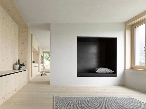 Plaster walls mixed with gray marble powder dominate the interior of the bottom floor, complementing its spruce wood carpentry. Photo 4 of House For Julia Björn modern home