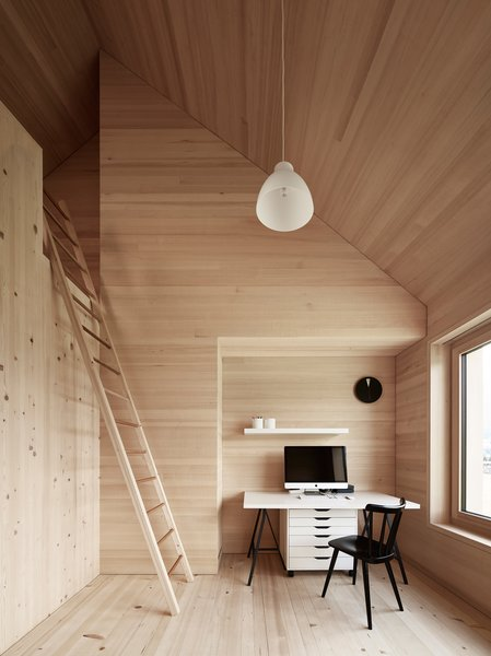 Spruce wood also lines the floor, walls, and ceiling in the bedrooms. The residents must climb a ladder to access the loft above. Photo 7 of House For Julia Björn modern home
