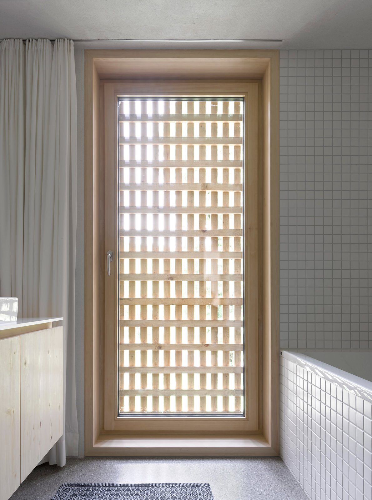 The latticework shell becomes a visual motif in the bathroom, furnished with appliances from Keramag, Kludi, and Laufen. A Simple Gabled House Features an Intricate Latticework Shell - Photo 9 of 10