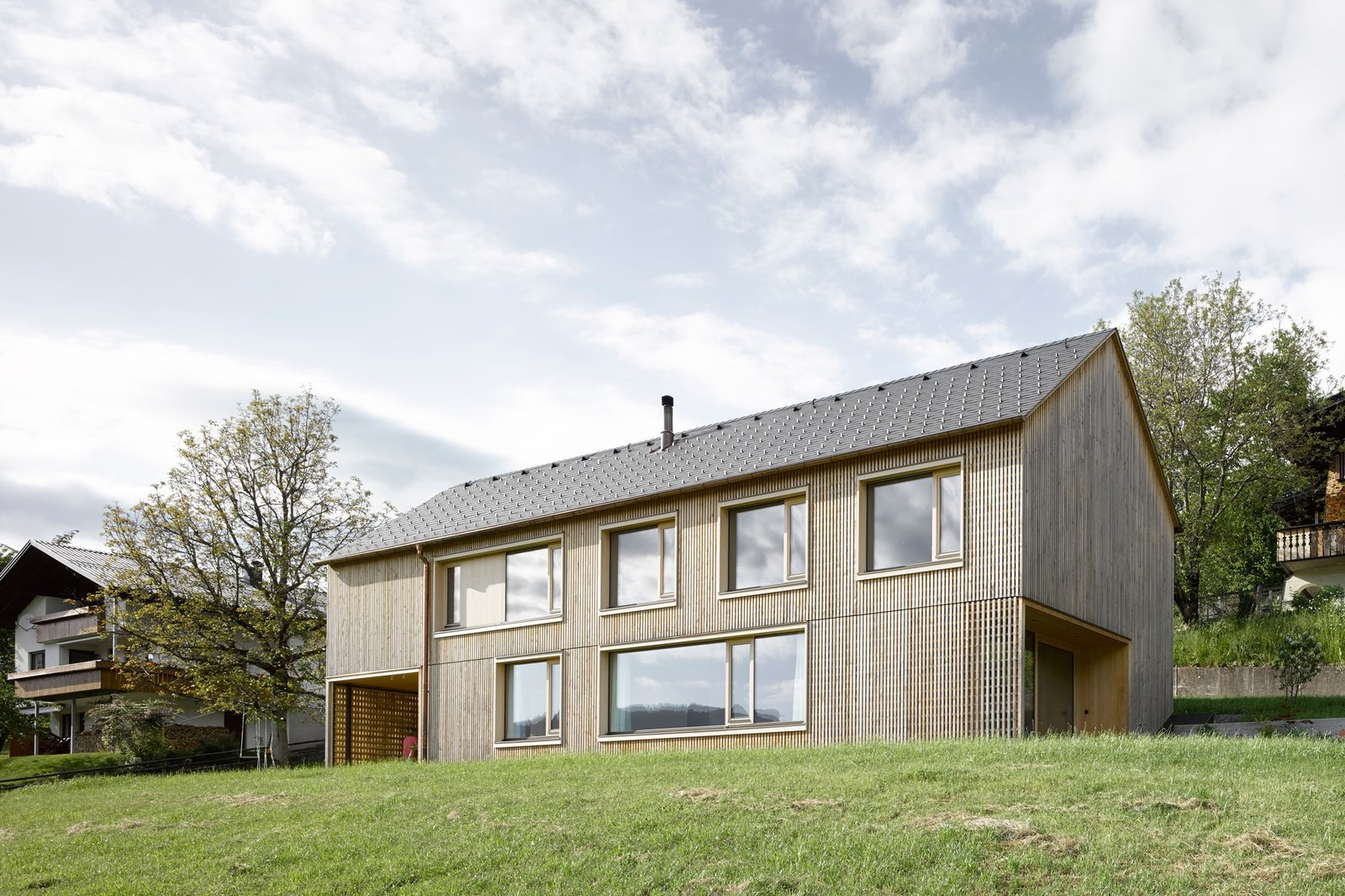 The house's simple gable form helps the house blend in with its neighbors.  Photo 10 of 10 in A Simple Gabled House Features an Intricate Latticework Shell from House For Julia Björn