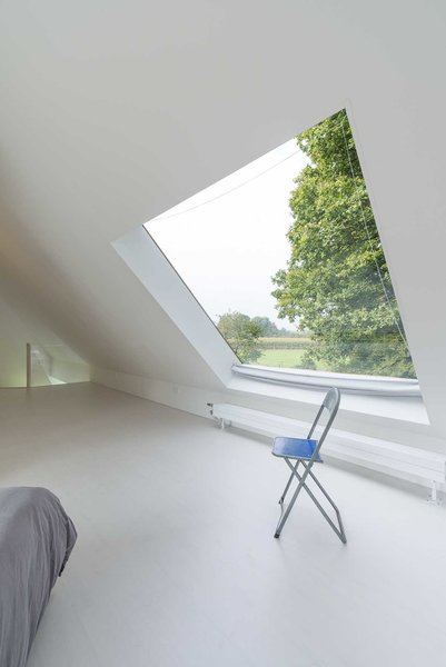 In the upstairs bedroom, a square skylight opens to a patch of sky. Photo 7 of Triangular House modern home