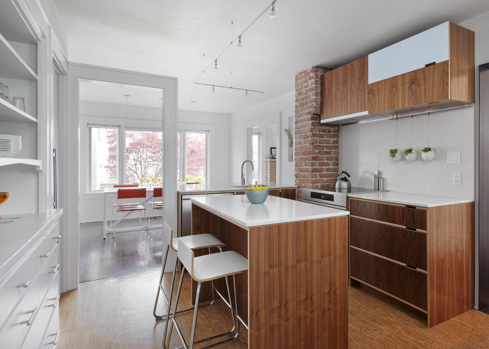 "A door frame was preserved as ""a sculptural memory piece,"" Sara Imhoff says, after a wall separating the old kitchen from a small dining room was demolished. The countertops and backsplash are by Caesarstone."