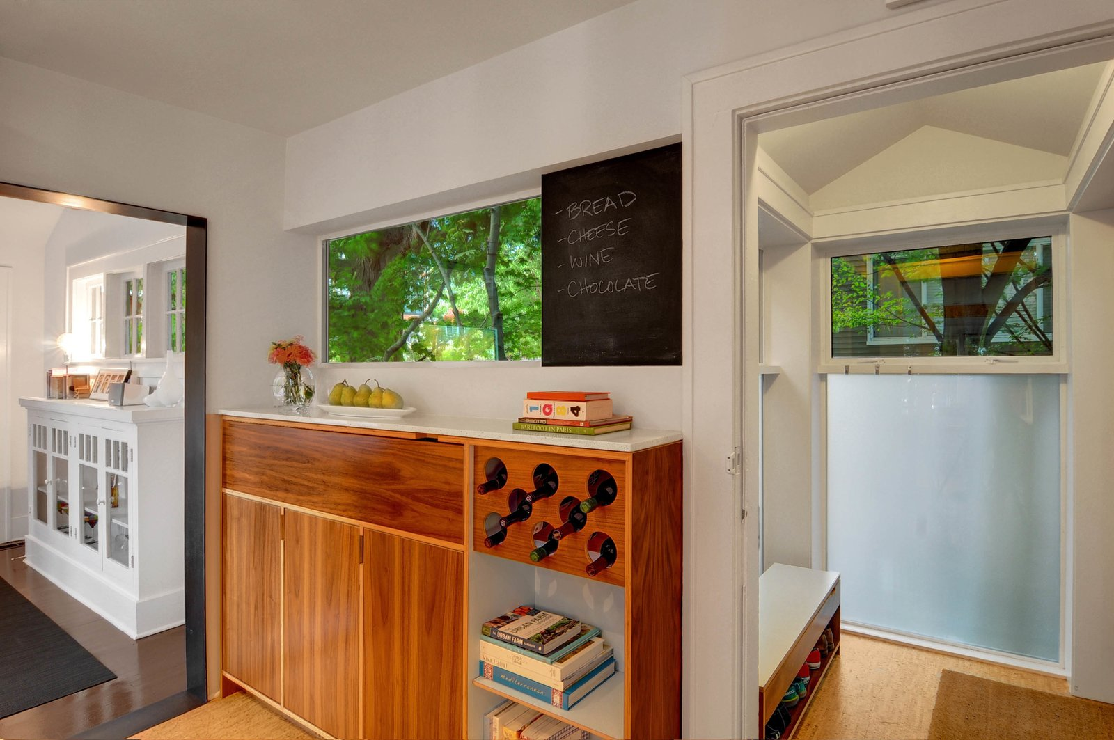 The Imhoffs designed the custom wine rack, which was built by KERF Design of Seattle. They enclosed an old side porch off the kitchen, transforming it into a mudroom.  Photo 6 of 7 in Transformative House Renovation in Seattle