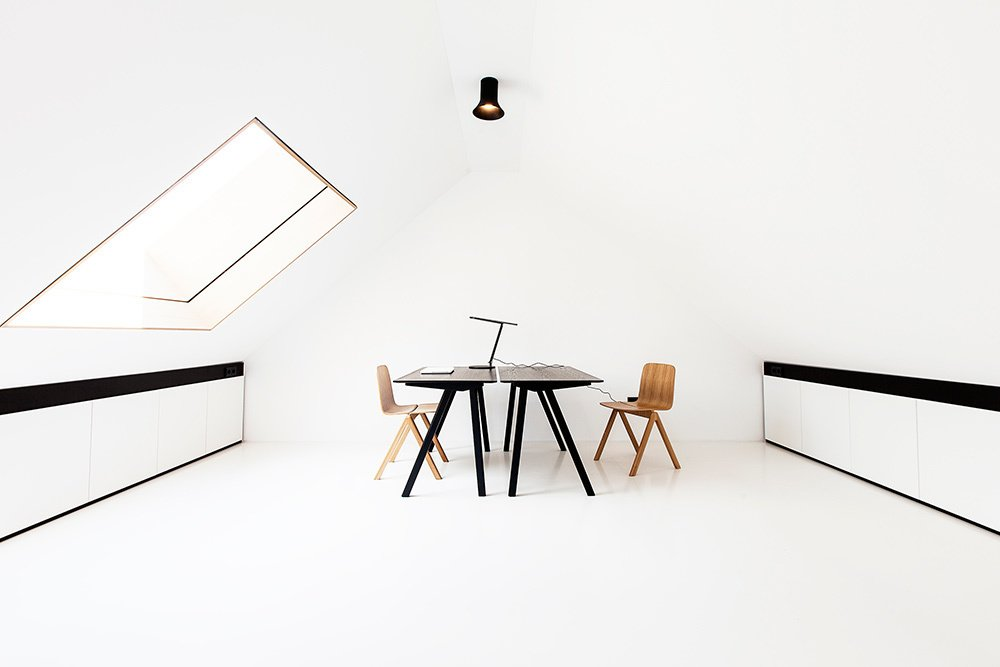 In the top floor study area, a pair of Copenhague Desks by Ronan & Erwan Bouroullec for HAY are stationed below a Sax hanging light by Vertigo Bird.