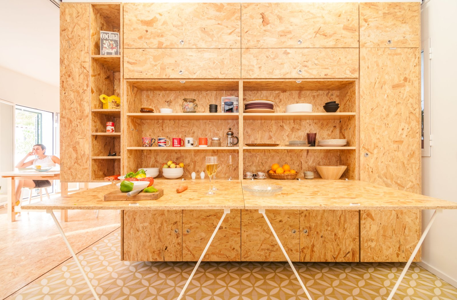 A drop-down countertop conceals dishware and other kitchen belongings.  Solutions For Tiny Kitchens by Aileen Kwun from Sliding Shelves Transform This Tiny Home Into Countless Configurations