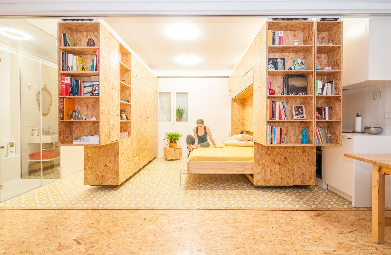 One of the shelving units includes a Murphy bed, making for a comfortable sleeping space. Tagged: Bedroom, Bed, Shelves, and Storage.  Storage by Dwell from Sliding Shelves Transform This Tiny Home Into Countless Configurations