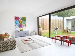 "The Best Prefab Homes in Australia - Photo 7 of 10 - The cozy ""rumpus room,"" a kids playroom that functions as a second living room, looks out onto the courtyard. The space was designed to encourage kids' creativity, while complementing adult tastes. With the addition of a movable wall, the space can be sectioned off so children can be seen but not heard. Functional and durable white cork flooring completes the child-friendly space."