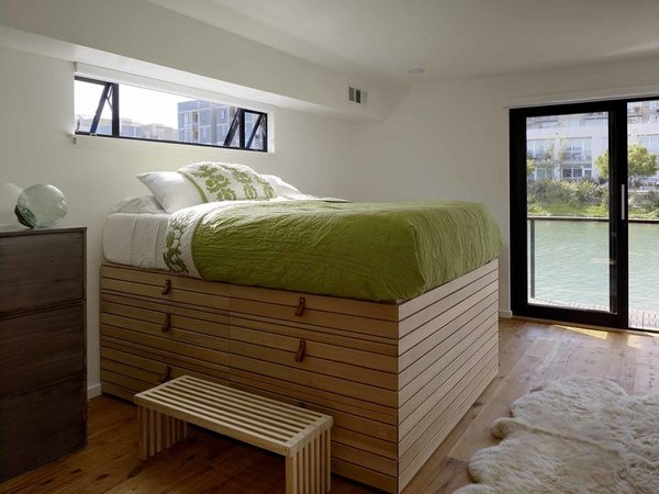 In the second floor master bedroom, a custom captain's bed designed by the homeowner, features drawers and storage underneath. Its towering height allows for views out the nearby window.