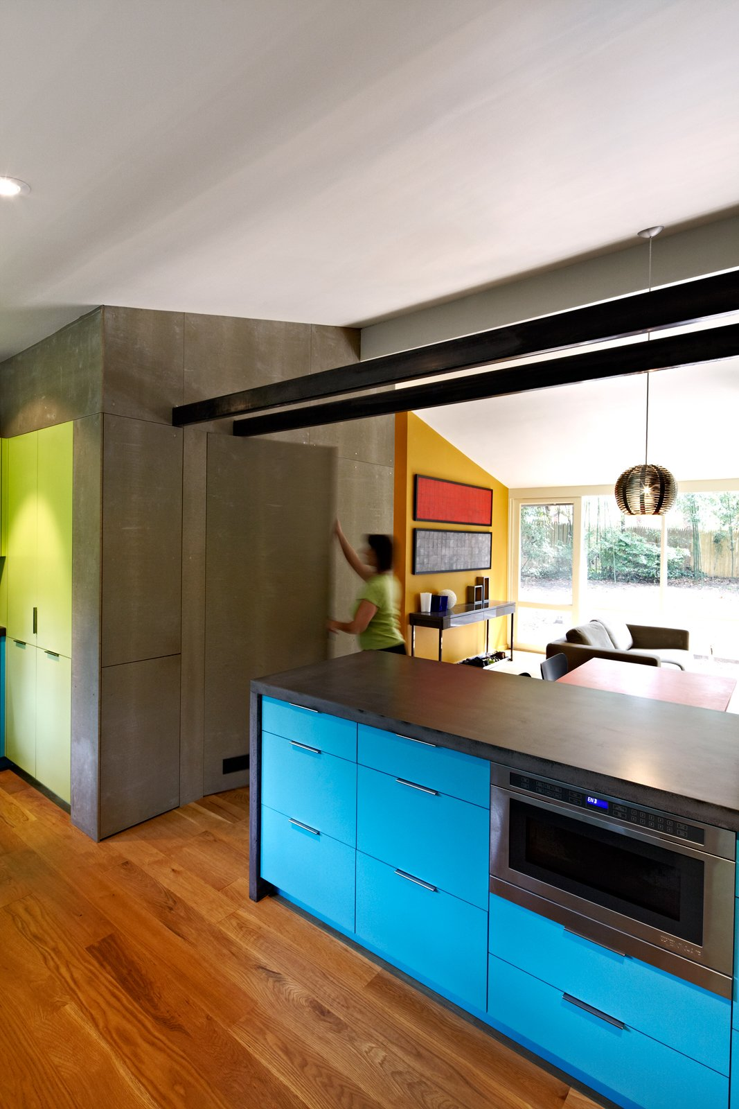A dark concrete counter and blue laminate cabinets surround the Jenn-Air microwave drawer in architect Janet Bloomberg's kitchen. The pendant hanging above the table is a Tejido Round Suspension from Artemide. Photo by: Greg Powers Tagged: Kitchen, Microwave, Pendant Lighting, Colorful Cabinet, and Medium Hardwood Floor.  Photo 2 of 6 in Modern Kitchen Renovation with Mid-Century Roots