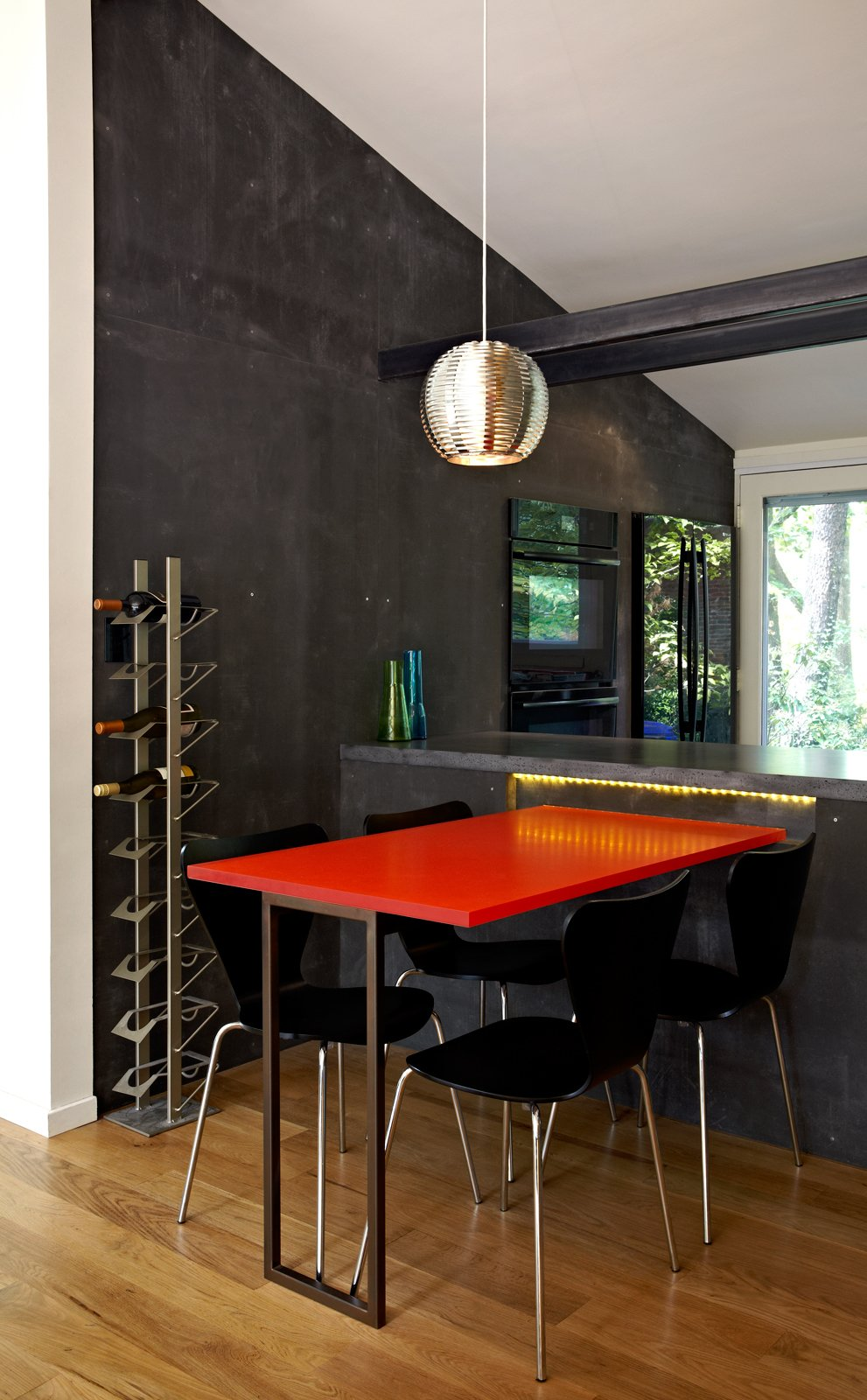 A new dining table, made from a leftover acrylic slab by 3form, sits on just the other side of the kitchen workstation. Photo by: Greg Powers  Photo 4 of 6 in Modern Kitchen Renovation with Mid-Century Roots