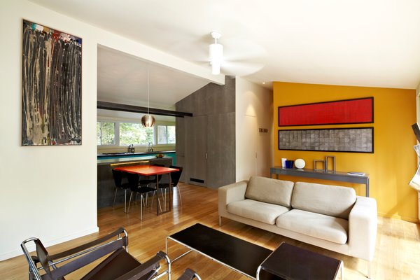 Today, Bloomberg's living room flows naturally into the kitchen. The living room's floor-to-ceiling glass windows offer loads of natural light to a previously tucked-away kitchen. The yellow wall and a few classic pieces of furniture from the modernist canon complete the renovation. Photo by: Greg Powers