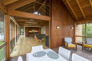 10 Enclosed Porches That Are Put to Good Use - Photo 1 of 10 - In a Cape Cod retreat, a sliding door opens to a relaxed screened-in porch. Varying types of wood make up the home's interior: white oak planks for the floor, solid mahogany for the cabinets, and fir for the ceilings, beams, columns, and trim.