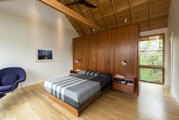 Four bedrooms occupy the bottom level. The beds are by Modernica and a Womb chair by Eero Saarinen sits in the corner.