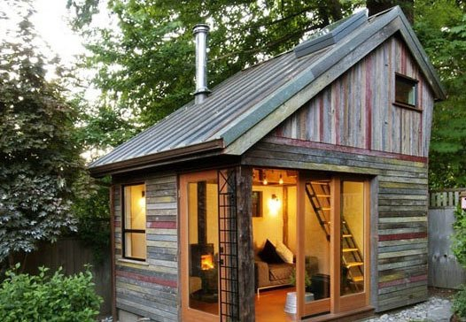 A polychrome facade made of salvaged, 100-year-old barnwood gives this small, lofted cottage space its unique character. Its copper roof is also reclaimed, a lucky Craigslist find from a local remodel. Though the structure has a footprint of just 11' x 14', it provides a useful space to entertain, catch up on work, or relax.  Outdoor by Suze from Backyard Escapes and Retreats We Love