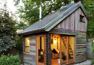 101 Best Modern Cabins - Photo 18 of 101 - A polychrome facade made of salvaged, 100-year-old barnwood gives this small, lofted cottage space its unique character. Its copper roof is also reclaimed, a lucky Craigslist find from a local remodel. Though the structure has a footprint of just 11' x 14', it provides a useful space to entertain, catch up on work, or relax.