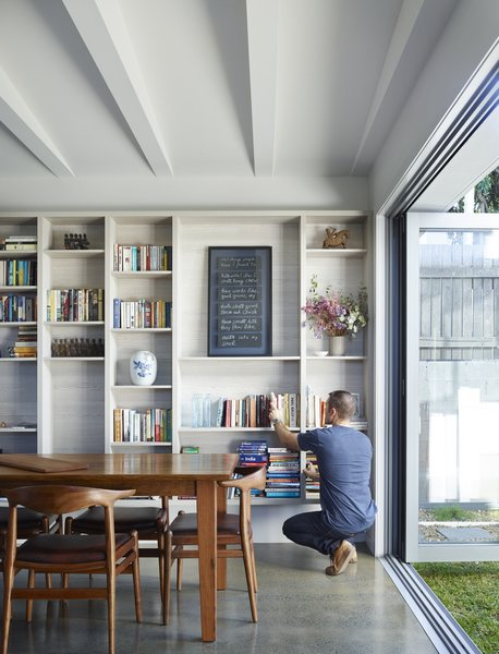"""Working with the narrow qualities of the site, the internal spaces of the kitchen and main living areas can open completely to double them in size,"" O'Neill said. The architecture firm built a custom bookshelf using drifted oak with the warm Ravine finish by Polytec. Photo 3 of Annie Street modern home"