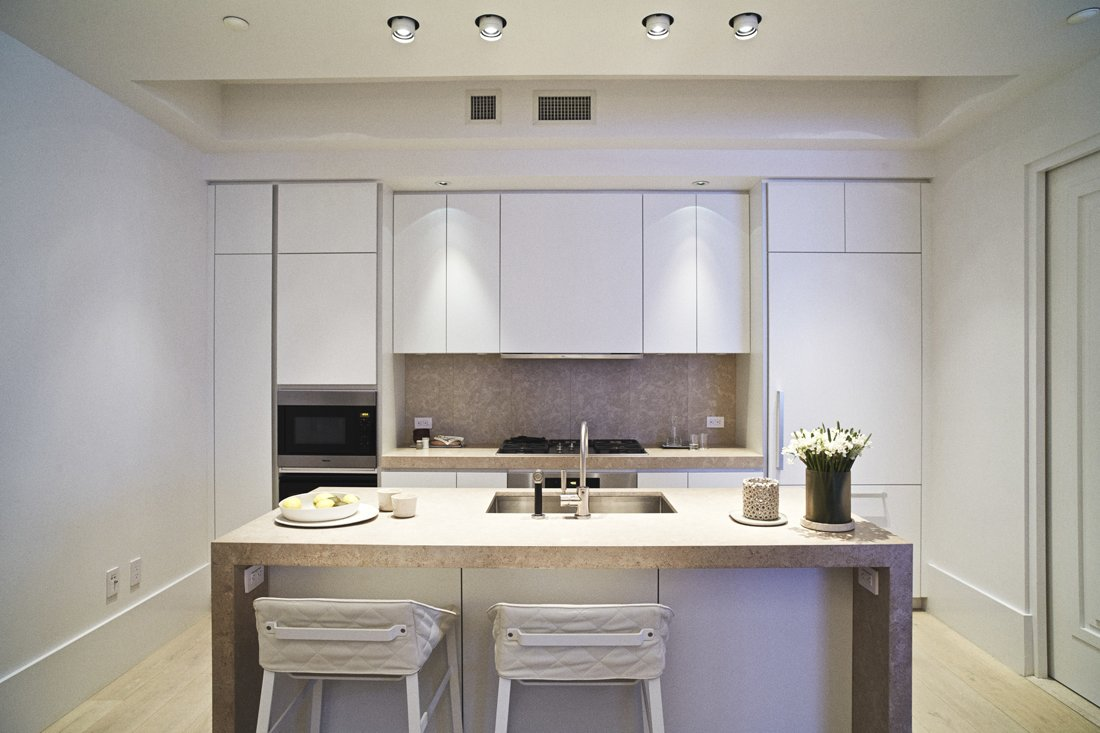 The kitchen of model unit 6C at Huys, 404 Park Avenue South, designed by Piet Boon with Karin Meyn. The kitchen sports white lacquer cabinetry by Bulthaup with a Chambolle marble countertop, Dornbracht fixtures, and Miele appliances.