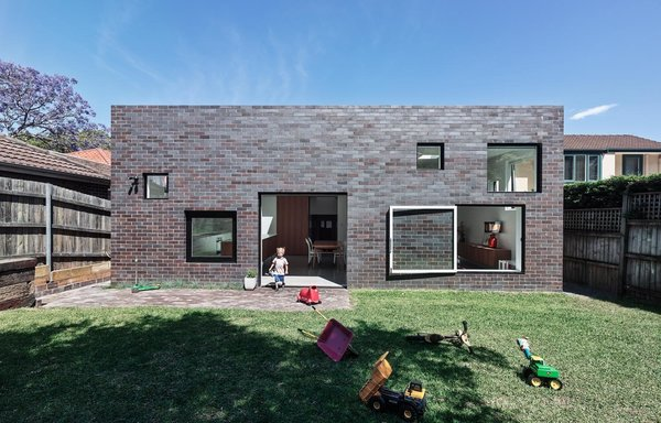 """The bungalow had beautiful bones but some major problems, including a poorly designed addition to the back that had to be removed. In its place, Tribe Studio designed a gray brick box that connects directly to the garden. """"The owners love the fact that the extension is compatible with the old part of the house, and is completely different from many renovations of this type, which simply open up the back in a single move,"""" Tribe says."""