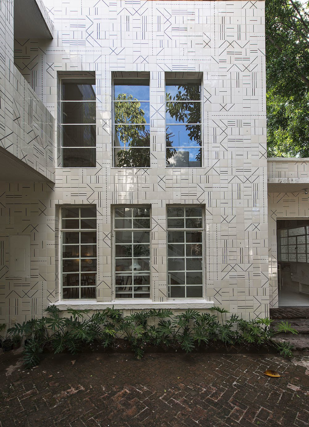 Located in a former artist's studio in a hip area of Jalisco, the restaurant is adorned with José Noé Suro custom ceramic tiles, inspired by the patterns made by local weavers. The pattern also reflects the kitchen's ad-hoc, irreverent style.  Photo 2 of 9 in 10,000 Bones Cover the Walls of this Mexico Restaurant
