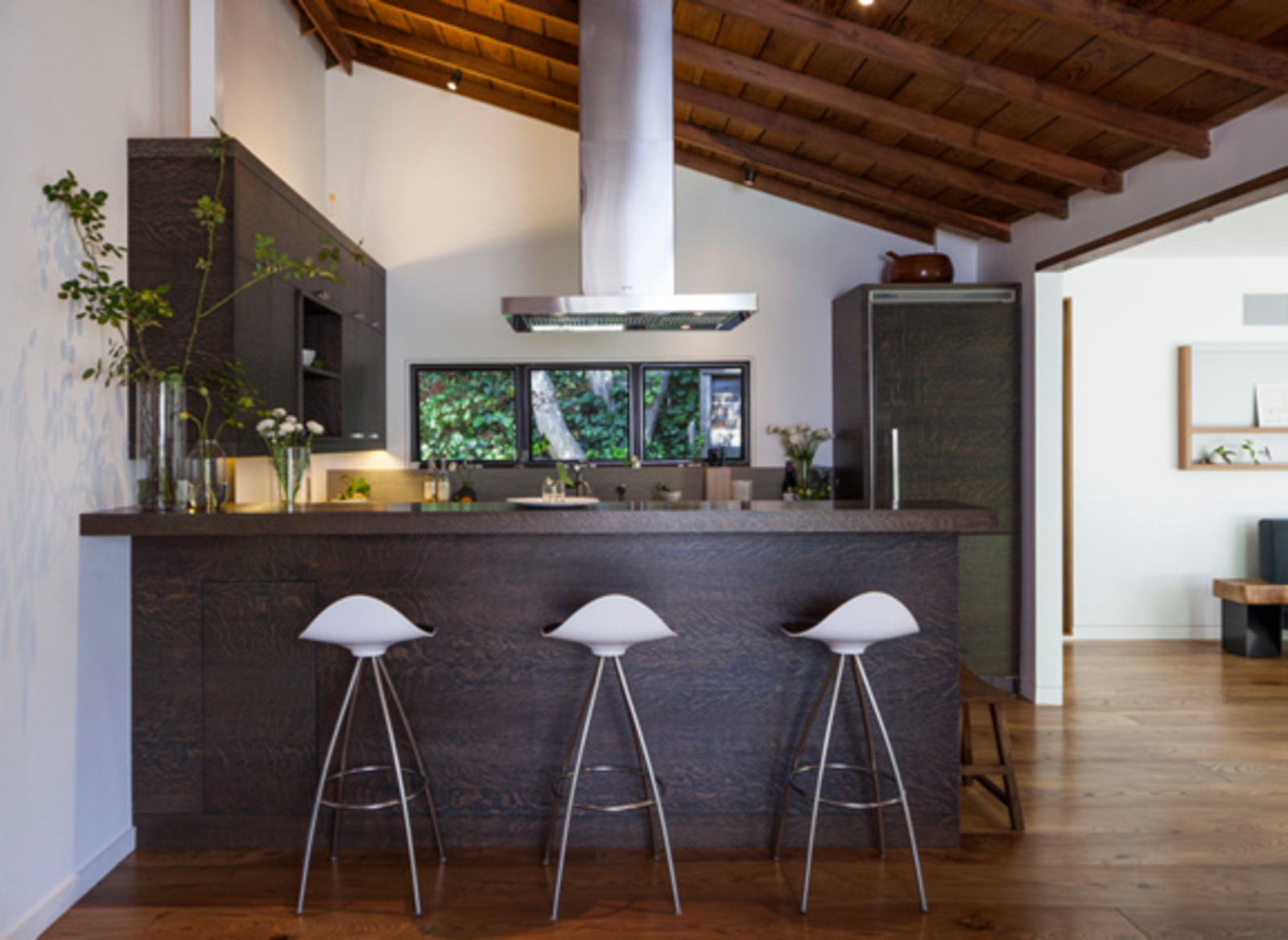 A new kitchen in the old part of the building contrasts sleek dark wood millwork with the original vaulted ceilings, which Gargan and Wagner scrubbed and sanded themselves to reveal the old-growth redwood.  Kitchen by Jeremiah Otis from Inside a Renovated Cottage in Marin