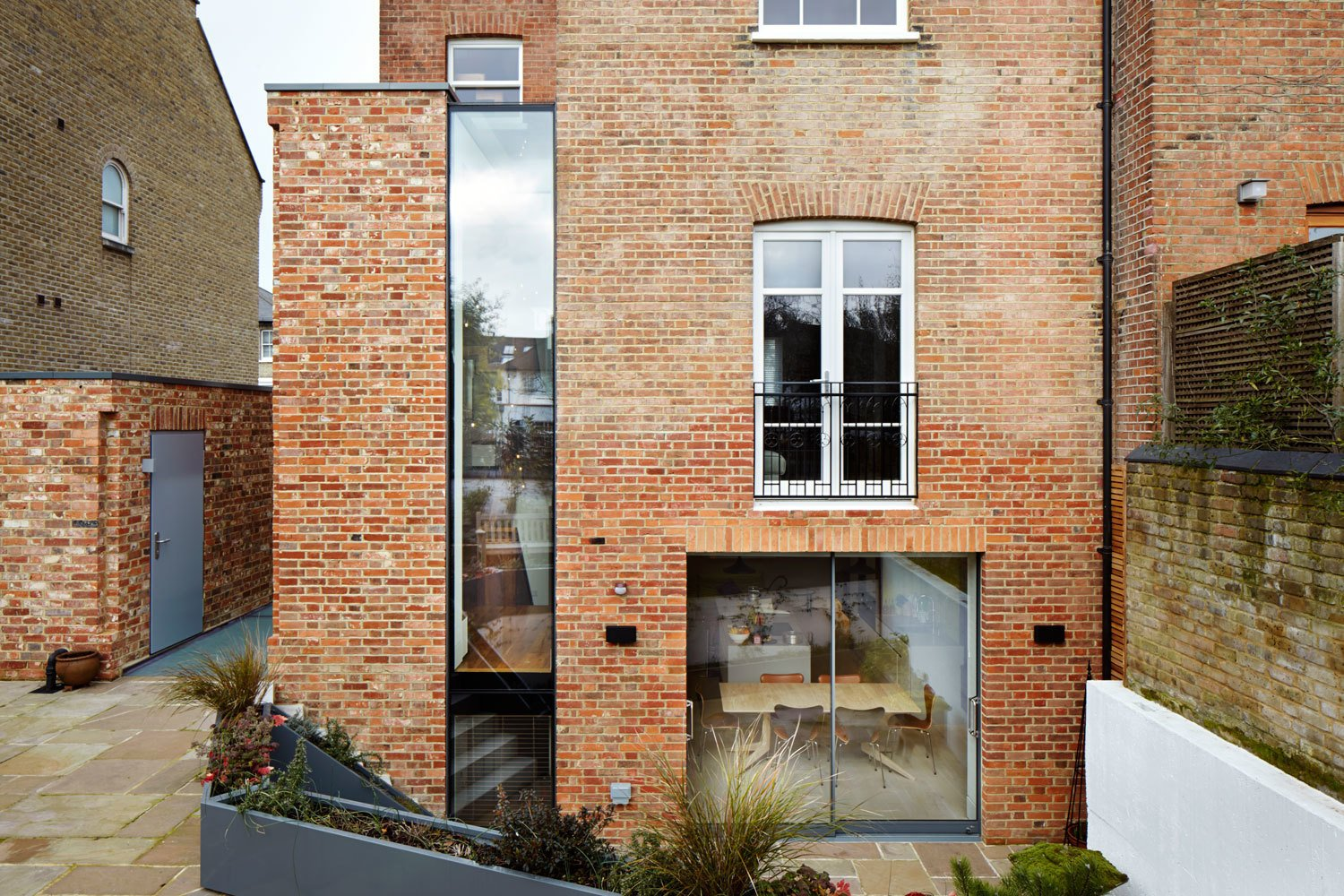 A tall and narrow window separates the new brickwork from the historic building, making its lines and profile clearly understandable.
